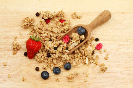 wooden scoop: Granola with fresh strawberry,blueberries and a wooden scoop on a chopping board Stock Photo