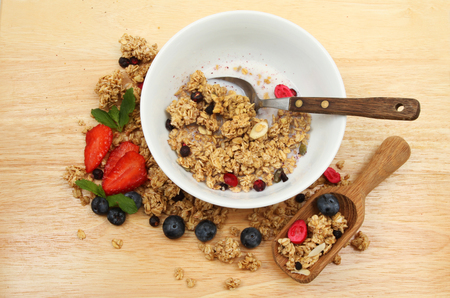 wooden scoop: Granola with milk in a bowl on a board with fresh fruit and a wooden scoop Stock Photo