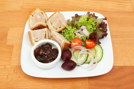 Pork pie, pickle and salad on a plate on a wooden tabletop