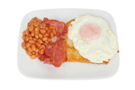 Bacon, fried egg, fried bread and baked beans on a plate isolated against white Stock Photo