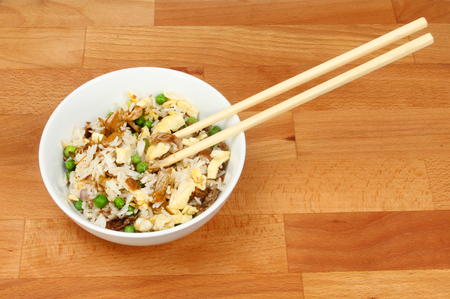 duck egg: Fried rice with chopsticks in a bowl on a wooden kitchen worktop