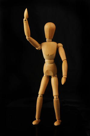 Wooden manikin isolated against black Stock Photo