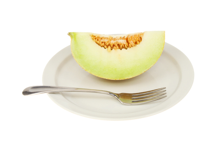 Galia melon portion on a plate with a fork isolated against white Stock Photo