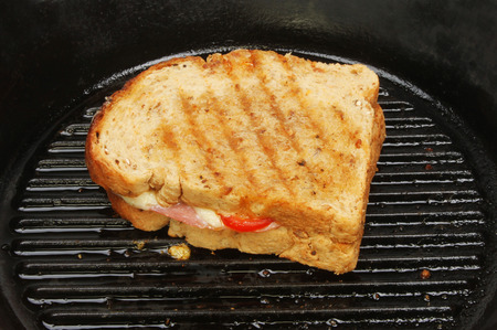 Toasted cheese, ham and tomato sandwich in a griddle pan