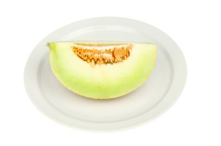 galia melon portion on a plate isolated against white