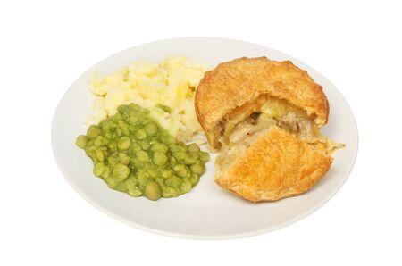 チキンとマッシュ ポテトと白に対する隔離板にどろどろエンドウ豆とマッシュルームのパイ