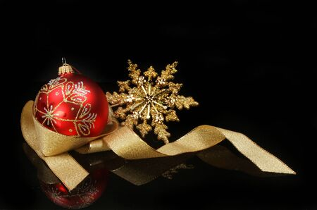 Christmas motif,red glitter bauble gold star and ribbon with reflections against a black background 写真素材