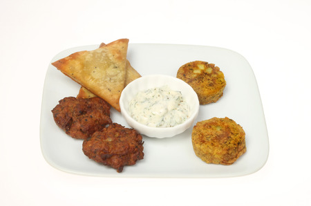 Indian snack selection with a dip on a plate isolated against white
