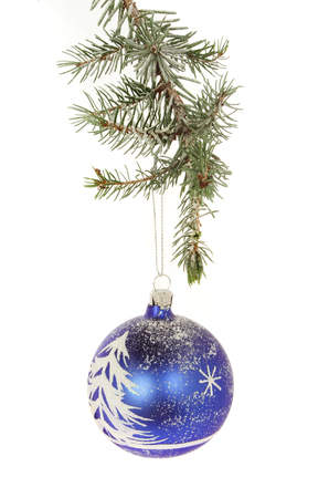 Snow scene Christmas bauble hanging from a snow dusted conifer branch Stock Photo