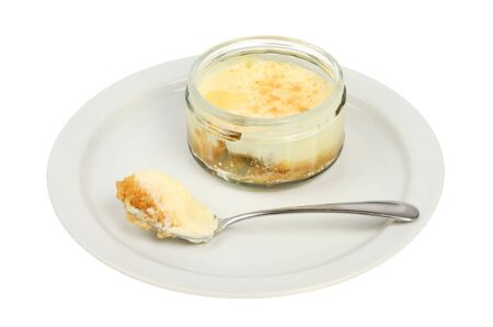 Lemon cheesecake in a ramekin with a spoon on a plate isolated against white