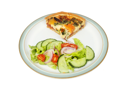 Mediterranean vegetable quiche and salad on a plate isolated against white Stock Photo