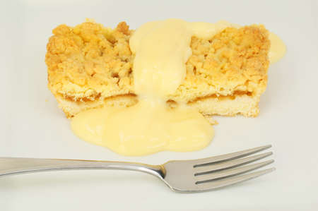 Closeup of apple crumble and custard with a fork on a plate