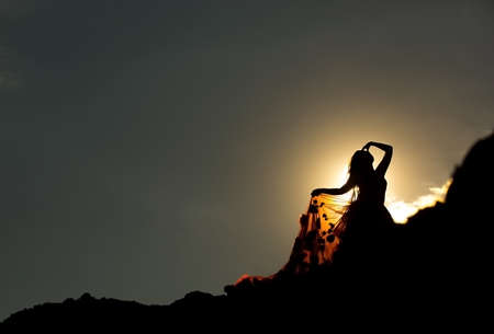 Woman silhouette in mountains, sunset Stock Photo