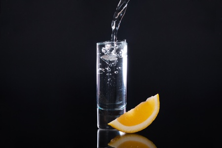 Shot glass filled with clear alcohol on a black background photo