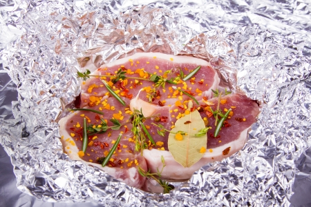 Raw fresh meat in foil with condiments photo