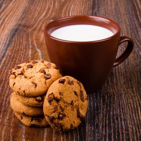 bizcochos: Galletas de chocolate y una taza de leche Foto de archivo