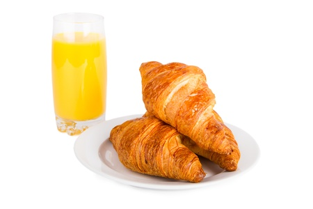 Croissants on a white plate and glass of orange juice. Isolated on white. photo