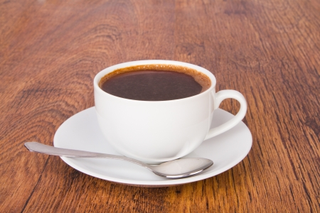 A cup of coffee on a wooden background photo