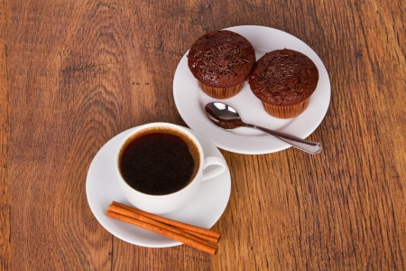 A cup of coffee with chocolate muffins, on a wooden background photo