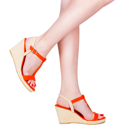 Woman legs wearing a pair of sandals, isolated on white photo