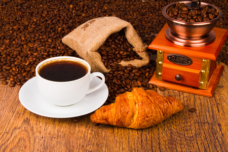 Coffee cup with a croissant and fresh coffee beans on a wooden background photo