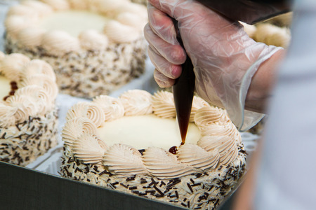 Chef decorate the cake with chocolate cream - Stock Image photo