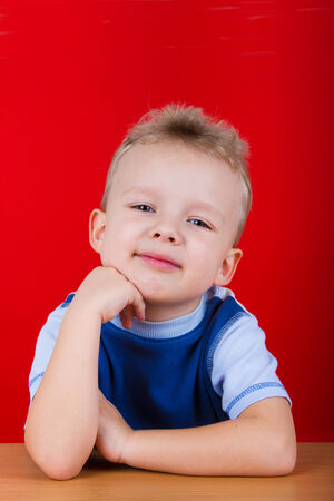 3 5 years: Small boy in blue T-shirt, sitting at the table. On a red background Stock Photo
