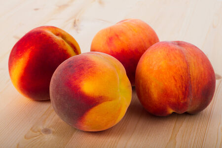 Fresh peaches on a light wood background