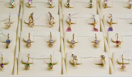 pietre preziose: Jewelry. Golden earrings with precious stones in a shop window. Archivio Fotografico
