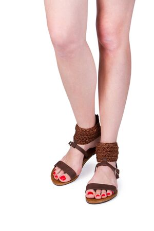 sandals isolated: Woman legs wearing a pair of sandals, isolated on white Stock Photo