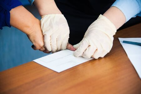 fingerprinting: The investigation of the crime. The inspector takes fingerprints of a suspect