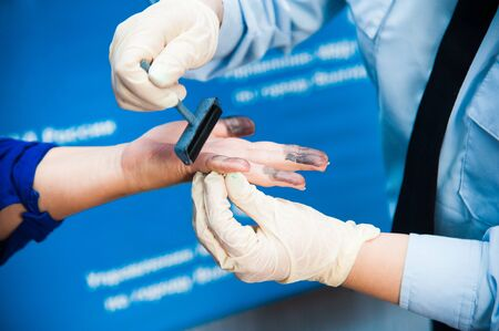 criminology: The investigation of the crime. The inspector takes fingerprints of a suspect