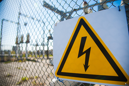 Electrical hazard sign placed on a metal fence Stock fotó
