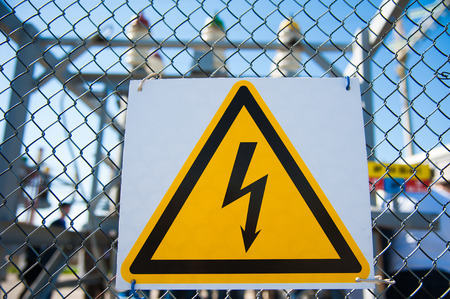 Electrical hazard sign placed on a metal fence Stock Photo