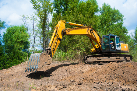 An excavator working removing earth on a construction site Stock Photo