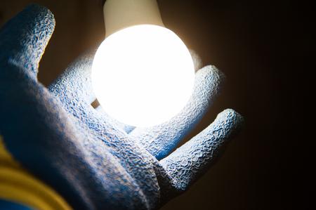 Hands holding new Light Emitting Diode ( LED ) light bulb with light