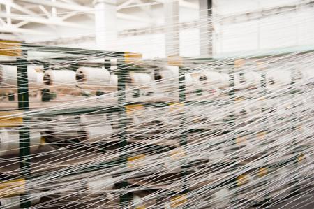 Textilindustrie - Garnspulen auf Spinnmaschine in einer Textilfabrik