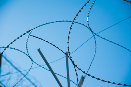 Barbed wire fence stretched around prison walls