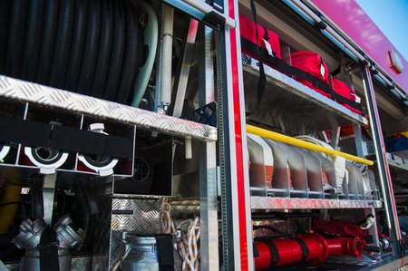 Compartment of rolled up fire hoses on a fire engine. Rescue fire truck equipment 免版税图像 - 105451673