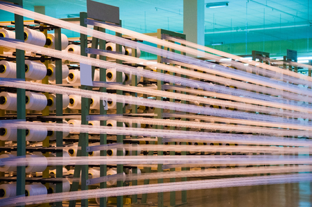 Industrial fabric production line. Weaving looms at a textile factory Standard-Bild - 108204995