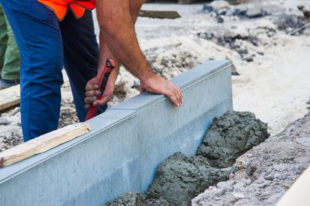 Proces budowy chodnika, montaż krawężnika pionowego