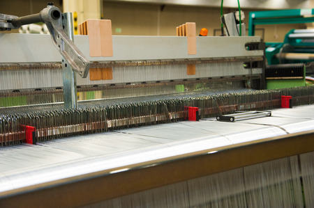 Industrial fabric production line. Weaving looms at a textile factory Standard-Bild - 113009488