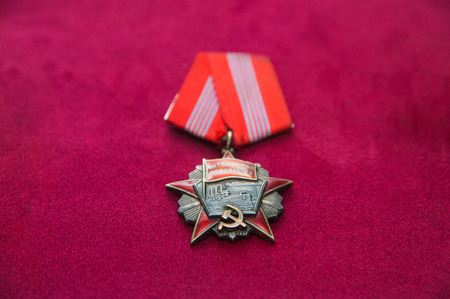 Old retro and modern military orders and military medals on red background Archivio Fotografico