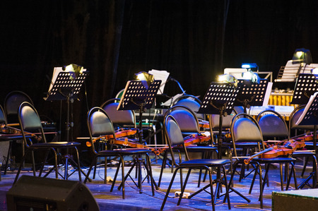 The stage is ready for the orchestra. Musical instruments, score, microphones. 版權商用圖片