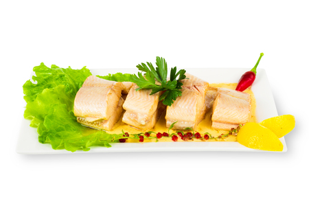 Dish of fish with greens and lemon on plate isolated on white