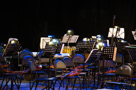 The stage is ready for the orchestra. Musical instruments, score, microphones. Stockfoto