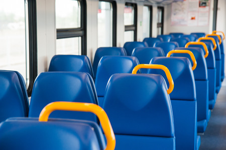 Inside of a train cabin with blue seats and sunlight coming in through the windows