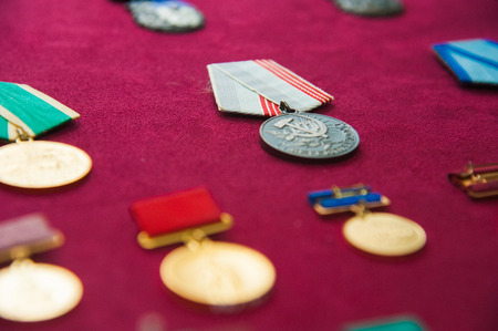 Old retro and modern military orders and military medals on red background Imagens