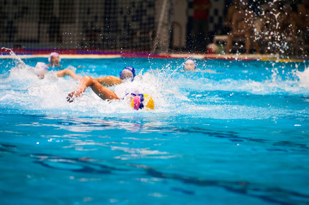 Water polo action in a swimming pool 写真素材