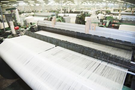 Industrial fabric production line. Weaving looms at a textile factory Imagens